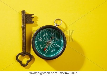 Old key and compass on a wooden background