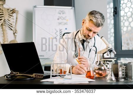 Senior Man, Research Scientist Writes Notes, Lab Observations. Male Researcher Carrying Out Scientif