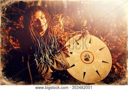 Beautiful Shamanic Girl Playing On Shaman Frame Drum In The Nature, Old Photo Effect.