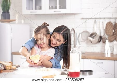 Mom And Daughter Prepare Pastries In The Kitchen.
