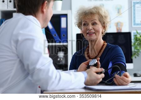 Male Doctor Measures Pressure An Elderly Woman. High-quality Procedures In Diagnostic Center. Preven