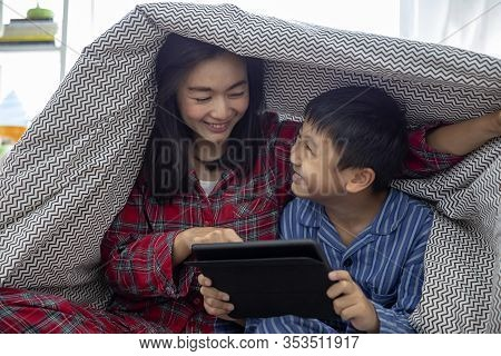 A Happy Asian Family Mother And Son Do Activity Together In Living Room Playing Game On Digital Tabl