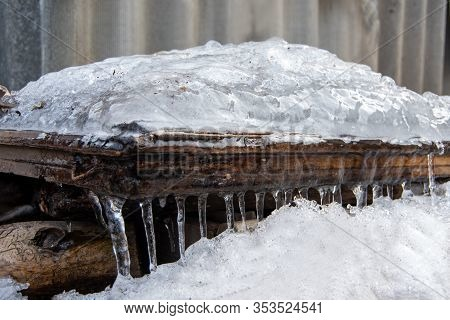 Icicles Hanging From The Roof Of A Wooden House In The Countryside Reach The Snow Cover. Perspective