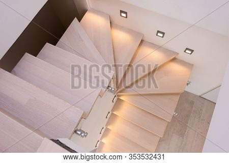 stylish interior with wooden stairs in big modern two level luxury apartment