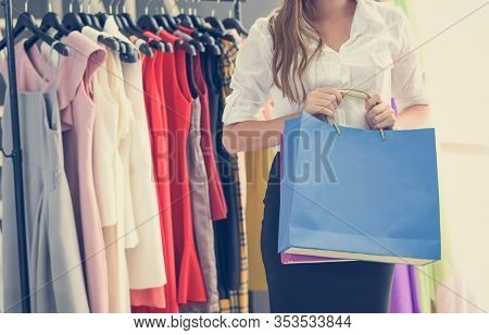 Woman Shopping And Holding Shopping Bag In Women Fashion Clothing Store With Colorful Women's Dresse
