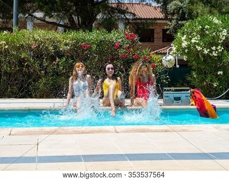 Three Girls From Different Ethnic Groups With Bathing Suits Of Different Colors Splashing The Water