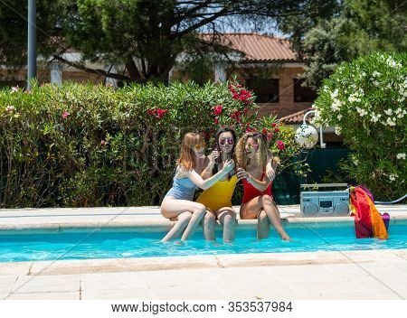 Three Girls Of Different Ethnicities With Bathing Suits Of Different Colors Toasting With Beer In A