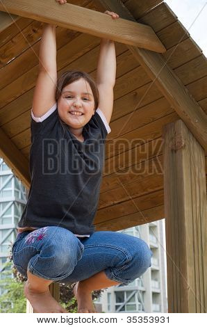 Smiling Young Girl Hanging On Wooden Structure