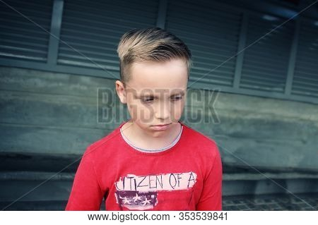 Cute Little Blue Eyed Caucasian Blond Boy Looks Sad And Frustrated. He Is Looking With Sorrow Pensiv