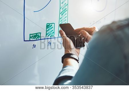 Man With Mobile Phone In Office In Front Of White Board