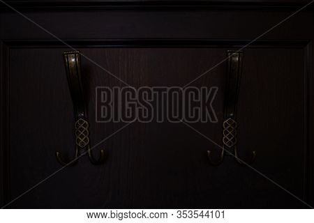 Forged Wall Coat Hanger With Two Hooks On A Dark Wooden Wall. Soft Selective Focus....