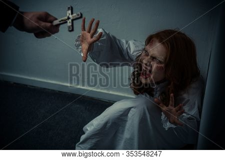 Exorcist Holding Cross In Front Of Screaming Obsessed Girl
