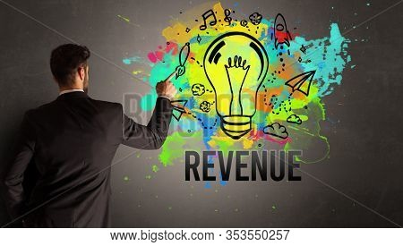 businessman drawing colorful light bulb with REVENUE inscription on textured concrete wall, new business idea concept