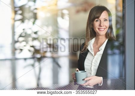 Happy businesswoman smiling in corporate workplace taking break and drinking coffee while standing at office window.
