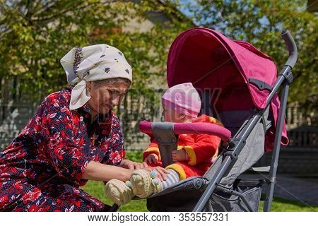 Putting On Shoes Baby In Stroller, A Baby Is Sitting In A Stroller And A Grandmother Is Tying Laces