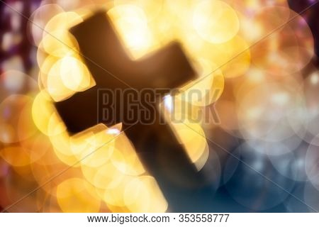 Abstract defocussed crucifixion cross silhouette in church interior against stained glass window concept for religion and  prayer