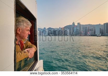 HONG KONG, CHINA - CIRCA JANUARY, 2019: man on a Star Ferry crossing Victoria Harbour. The Star Ferry is a passenger ferry service operator and tourist attraction in Hong Kong.