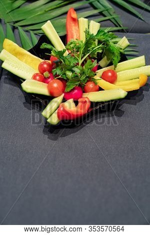 Plate With Sliced Vegetables On A Black Background. Freespace.