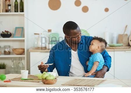 Portrait Of Happy African-american Dad Feeding Cute Little Boy White Sitting At Kitchen Table , Copy