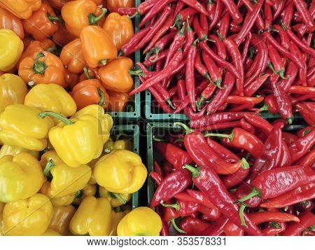 A Variety Of Sweet Yellow Peppers And Bitter Red On The Shelves In The Supermarket.