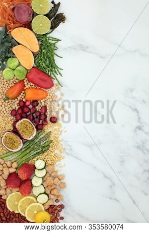 Vegan health food background border with foods high in protein, vitamins, minerals, antioxidants, anthocyanins, fibre, omega 3 and smart carbs. Ethical eating food concept. Flat lay on marble.