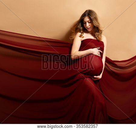 Pregnant Woman With Red Flying Fabric On Brown Background
