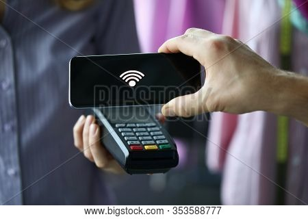 Man Through Terminal Using Pay Pass Technology. Phone With Contactless Payment Technology Allows You
