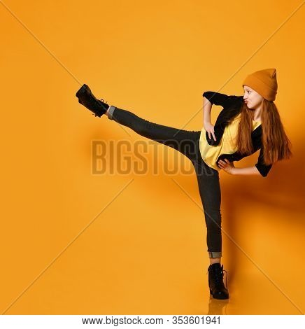 Cool And Frolic Girl With Long Red Hair In Hat, Black Tight Jeans And Brutal Shoes Is Kicking Holdin