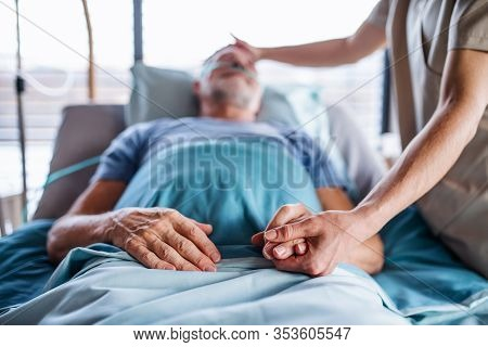 Unrecognizable Female Doctor Examining Senior Man In Bed In Hospital.