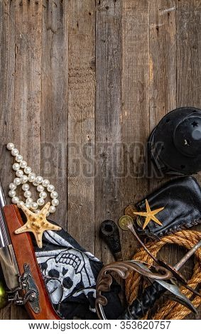Vintage Pirate Epee And Pistol Flag Jolly Roger And Other Medieval Outfit Lie On Empty Wooden Backgr