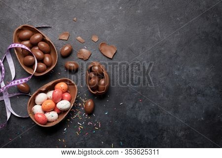 Chocolate easter eggs and colorful sweets on stone background greeting card. Top view with copy space. Flat lay