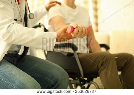 Handicapped Man Sits Working Out Dumbbell Arm. Rehabilitation After Injuries. Treatment And Restorat