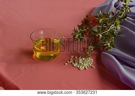 Safflower. Safflower Oil, Seeds And Stems With Flowers On A Pink Background.
