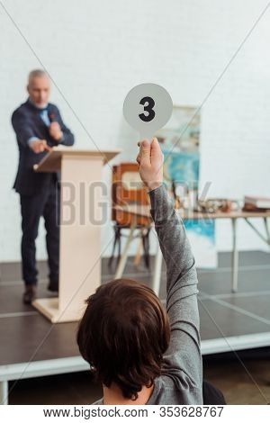 Back View Of Buyer Showing Auction Paddle With Number Three To Auctioneer During Auction