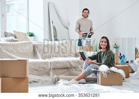 Pretty young woman and her husband with picture frames looking at you while unpacking boxes in their new house