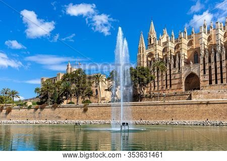 Fountain and Palma Cathedral on background under blue sky in Palma de Mallorca, Spain.