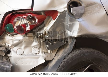 Rear Of A Vehicle After Suffering An Accident, With Several Broken Parts And With The Flat Tire. Con