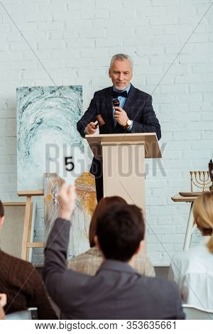 Selective Focus Of Smiling Auctioneer Talking With Microphone And Looking At Buyer During Auction
