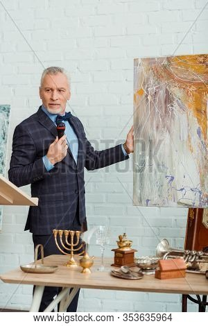 Auctioneer Talking With Microphone And Holding Picture During Auction
