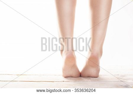 Female, Healthy Feet, Standing On Tiptoes On Wood Floor On A White Background.