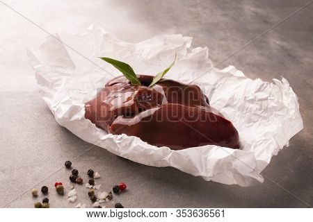 Raw Pork Livers On A Paper On A Stony Worktop. Pig Meat, Giblets.