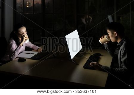 Young adult asian businessman and woman drinking hot cofee while working late at night in their office with desktop computer and laptop. Using as hard working and working late concept.