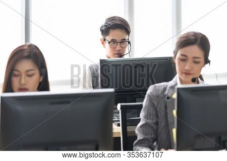 Young adult friendly and confidence operator with headsets working in a call center with her colleague team working.