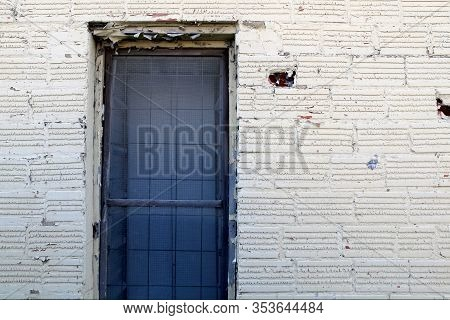 An Old Alley Whitewashed Brick Wall With Locked Blue Gate Door