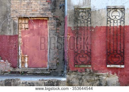A Red Fadeing Painted Dirty Warehouse In An Alley With Red Door Rusted And Concrete Steps