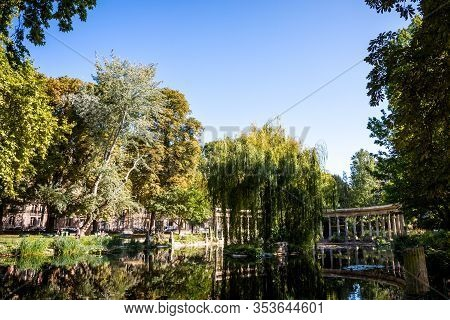 Corinthian Colonnade And Pond In Parc Monceau Gardens, Paris, France