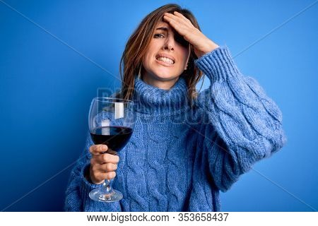 Young beautiful brunette woman drinking glass of red wine over isolated blue background stressed with hand on head, shocked with shame and surprise face, angry and frustrated. Fear and upset