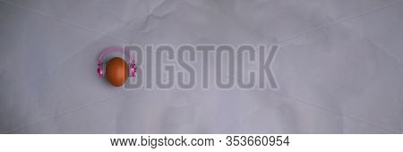 Easter Egg With Pink Headphones On Gray Background With Copyspace. Banner Of Macro Moody Minimalisti