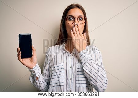 Young beautiful brunette woman holding smartphone showing screen over white background cover mouth with hand shocked with shame for mistake, expression of fear, scared in silence, secret concept