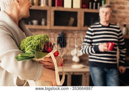 Groceries For Cooking. Elderly Couple Unpacking Eco Bag With Organic Vegetables In Kitchen After Foo